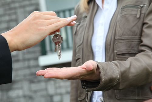 Agent handing keys to buyer – Reasons to purchase real estate in off season