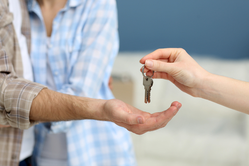 woman's hand handing new apartment keys to male hand