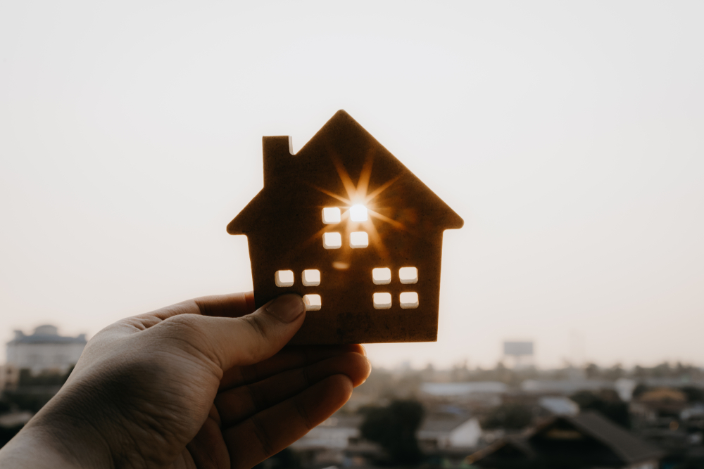Hand holding house cutout, sunlight