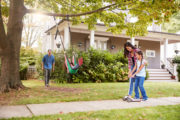 Happy family playing in front yard – Idaho rates high a great place to raise family