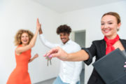 Happy landlord holding keys, happy tenants doing high five