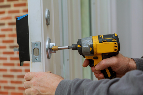 Man repairing lock on door – Rental property safety maintenance tips