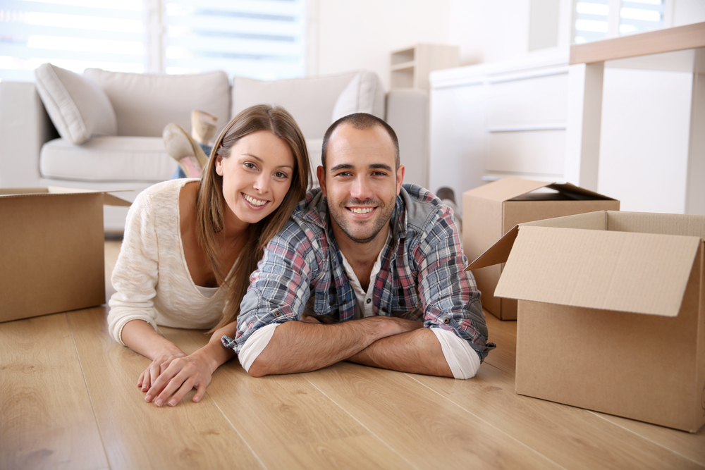 Smiling couple on floor, moving boxes, nice room