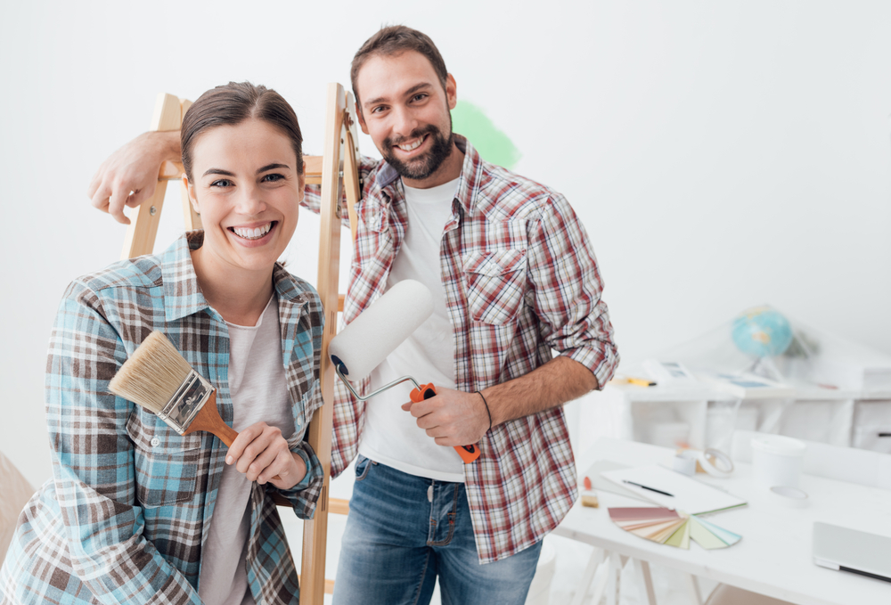 smiling couple renovating home, house flipping