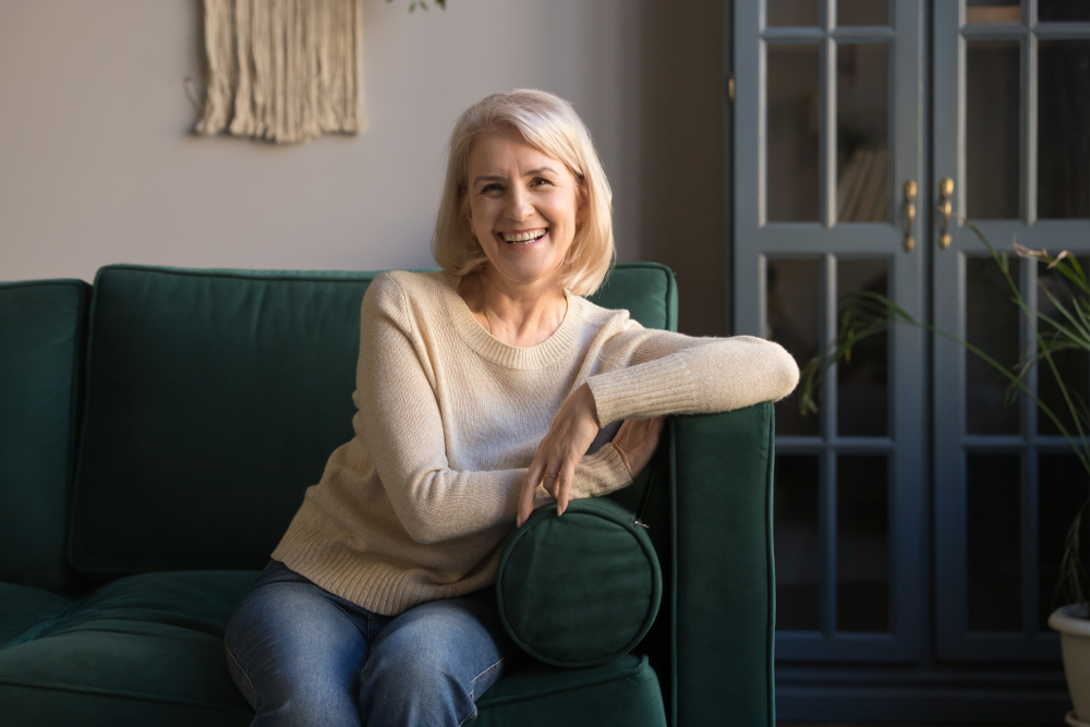 smiling older woman sitting on sofa, mother-in-law apartment