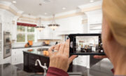 woman taking photo of kitchen, real estate listing