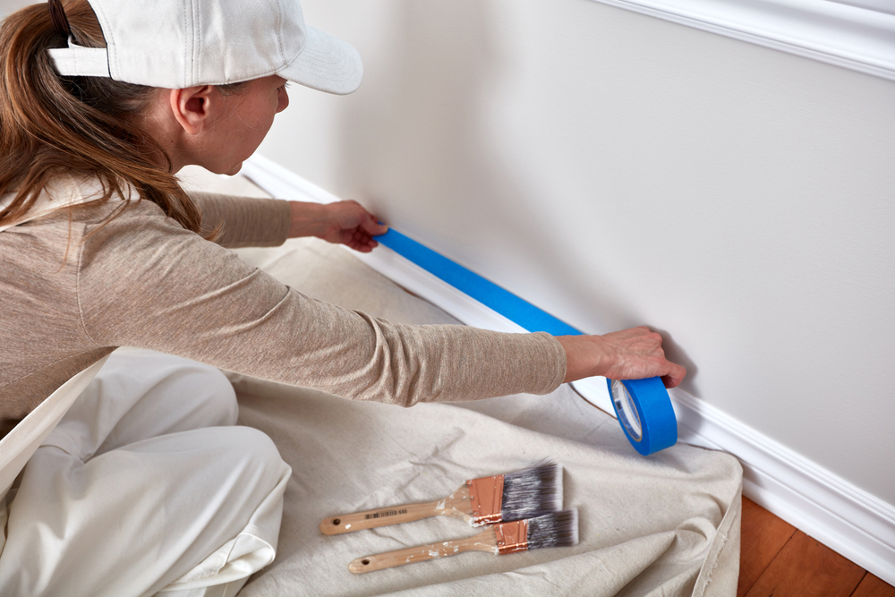 Woman with painters tape, paint brushes, taping wall